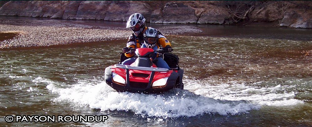 Picture from the Payson Roundup, of an ATV forging up a wet creek bed.